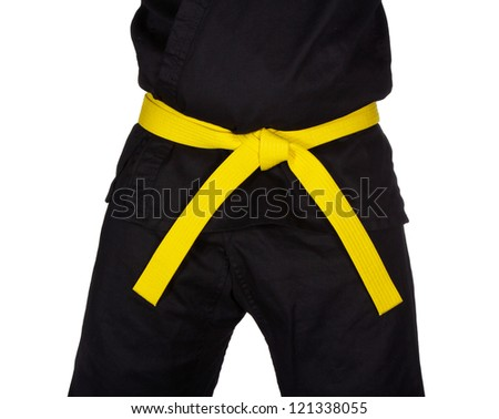Karate yellow belt tied around marital artists torso wearing black dojo GI's.