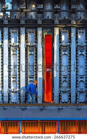 KARDEMIR, TURKEY - SEPTEMBER 6, 2013: Unknown worker cleans fallen coke from an open oven on the battery, Turkey on September 2013. Coke battery in Kardemir Karabuk Iron and Steel Industry and Trade - stock photo