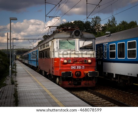Karez, Czech Republic - August 11, 2016 - Passenger train leaded with old red and cream white electric locomotive no. 242 213-7 of CD company. Other railroad passenger car behind.