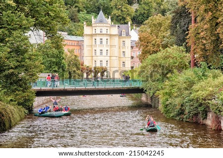 KARLOVY VARY, CZECH REPUBLIC - SEPTEMBER 15 2012: Tourists paddle canoes on Tepla River in famous spa town renowned for thermal baths, medical tourism and beautiful, pastel, elaborate architecture. - stock photo