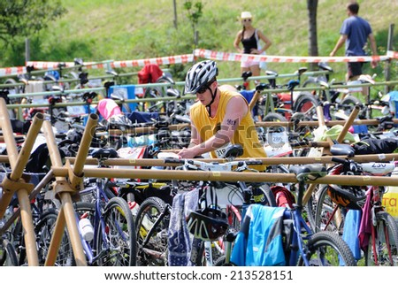 KAROLINKA, CZECH REPUBLIC - AUGUST 08, 2014: Male racer takes his bicycle in depo at the Valachia Man triathlon - stock photo