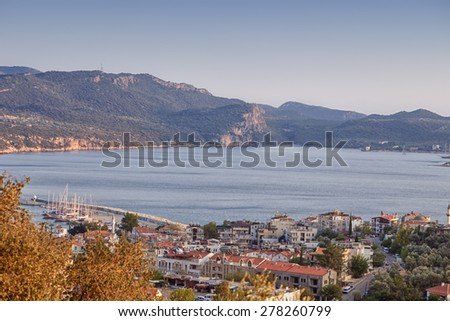 KAS, TURKEY - OCTOBER 15, 2009: View of the Turkish Riviera with fishing village Kas in Turkey at sunset. Kas is a small fishing, diving, yachting and tourist town and part of Antalya Province.  - stock photo