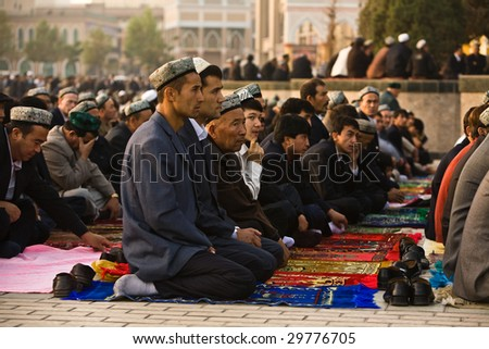 KASHGAR, CHINA - OCT 2 : Muslim worshipers kneel on prayer carpets outside of Id Kah Mosque at the end of Ramadan month October 2, 2008 in Kashgar,  Xinjiang province western China.