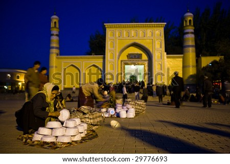 KASHGAR, CHINA - OCT. 2 : Uyghur women sell Muslim skull caps in front of Id Kah Mosque before dawn on the last day of Ramadan October 2, 2008 in Kashgar,  Xinjiang province western China.