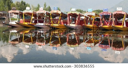KASHMIR, INDIA - AUG 3 Shikara boats on Dal Lake with houseboats in Srinagar - Shikara is a small boat used for transportation in the Dal lake - 3rd of August 2013, Srinagar, Jammu and Kashmir, India
