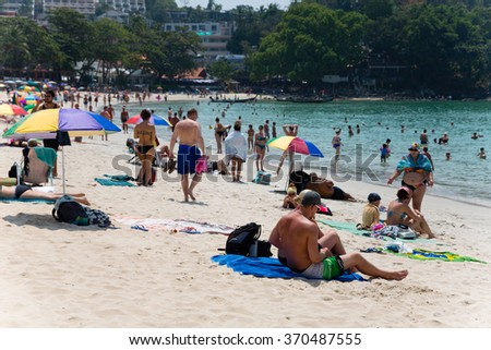 KATA BEACH, THAILAND - CIRCA FEBRUARY, 2015:  People relax on Kata beach. This is one of the most popular beaches among tourists in Phuket.  - stock photo