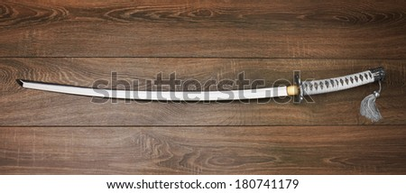 Katana, japanese sword, on wood background - stock photo