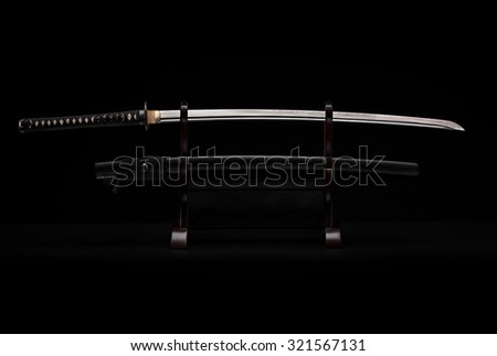 Katana sward in the stand on the black background - stock photo