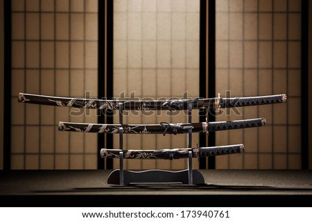 Katana, wakizashi and tanto on stand in a room, yellow background - stock photo