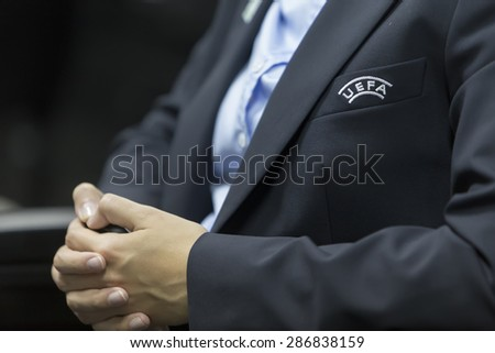 KATERINI, GREECE, JUNE 9,2015: Unspesific Uefa man with pin and costume during the Uefa Under19 Championship draw. - stock photo