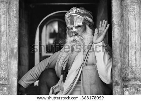 KATHMANDU - APRIL 14: A sadhu at Pashupatinath Temple in Kathmandu, Nepal on April 14, 2012. Sadhus are holy men who have chosen to live an ascetic life and focus on the spiritual practice of Hinduism - stock photo