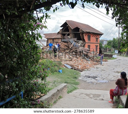 KATHMANDU - APRIL 26: Nepalese woman looks at a collapsed house after earthquake, near Lalitpur district, end of April 2015, Kathmandu, Nepal - stock photo