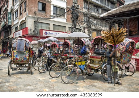 Kathmandu, Nepal - April 16, 2016: Group of rickshaws by the street at Asan Tole Market which is busy with workers, local and tourists.