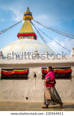 KATHMANDU, NEPAL - APRIL 1, 2013: Nepalese woman walking around Boudhanath stupa on April 1, 2013 in Kathmandu. Boudhanath stupa is the center of Buddhism pilgrimage in Nepal. - stock photo