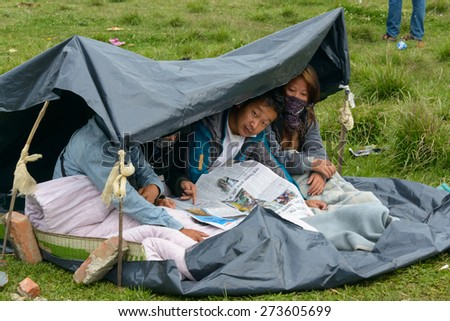 KATHMANDU, NEPAL - APRIL 26, 2015: People read the papers on an open ground at Chuchepati after their first night outside after the 7.8 earthquake on 25 April 2015. - stock photo