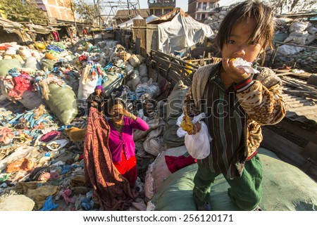 KATHMANDU, NEPAL - CIRCA DEC, 2013: Unidentified child and his parents during lunch in break between working on dump. Only 35% of population Nepal have access to adequate sanitation. - stock photo