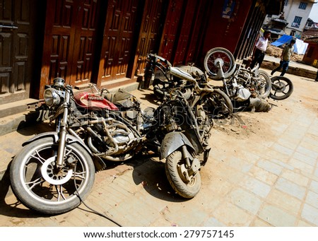 KATHMANDU, NEPAL - MAY 14, 2015: Crushed motorbikes are left in a street near Durbar Square after two major earthquakes hit Nepal in the past weeks. - stock photo