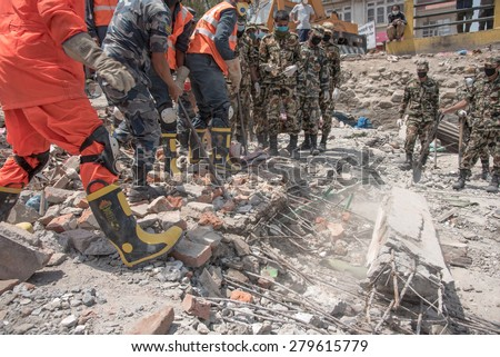 KATHMANDU, NEPAL - MAY 1, 2015: soldiers with debris of buildings near Sobhavagbati bridge damaged after the major earthquake on 25 April 2015.