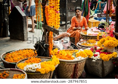 KATHMANDU, NEPAL / NEPAL - JUNE 10 2013 - Unidentified woman, selling flowers to the people who visits the local temple. - stock photo