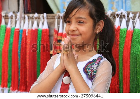 Kathmandu, Nepal- Nepalese young girl hands together to do namaste on April 18, 2014 - stock photo
