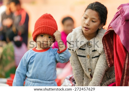 KATHMANDU,NEPAL,NOVEMBER 04,2010: A little boy wearing a red woolly hat is posing at the street market in the historical Patan Durbar square in Kathmandu, Nepal - stock photo