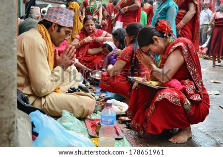 Kathmandu, Nepal - September 18, 2012: Hindu Brahmin blessing youngin girl in traditional red sari on celebration the Haritalika Teej festival on Durbar square in Kathmandu, Nepal - stock photo