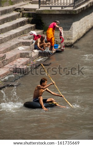 KATHMANDU, NEPAL - SEPTEMBER 21: Nepali people washing clothes and swimming at holy Bagmati River during cremation ceremony at Pashupatinath temple on Sept 21, 2012 in Nepal, Kathmandu, Pashupatinath