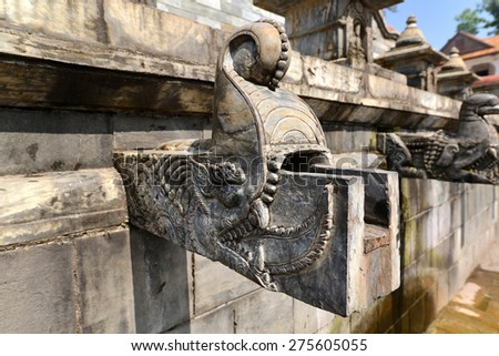 KATHMANDU - OCTOBER 10: Carved stone fountain in Pashupatinath. The fountain was destroyed after that earthquake hit Nepal on April 25, 2015. On Oct. 10, 2013 in Kathmandu, Nepal - stock photo