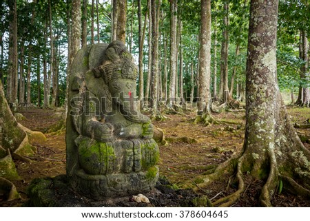 Kauai, Hawaii February 12, 2016 - Ganesha is the deity of wisdom, knowledge & new beginnings. This hand carved statue is amongst Moreton Bay Fig trees at the Hindu Himalayan Academy on Kauai