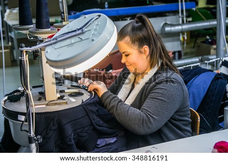 KAUNAS, LITHUANIA - DECEMBER 8, 2015: Woman working on textile clothes factory