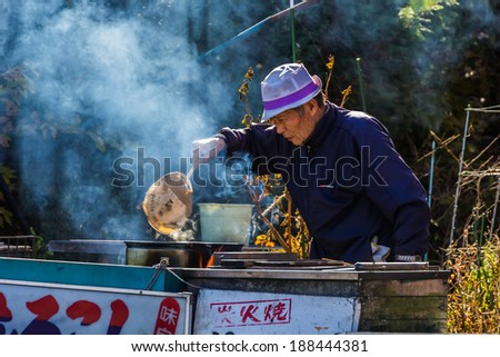 KAWAGUCHIKO, JAPAN - NOVEMBER 22: Senior citizen in Kawaguchiko, Japan on November 22, 2013. Unidentified senior male sets fire boiling corn in the kettle to sell to tourist on the side of the road