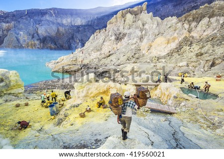 Kawah Ijen, East Java, Indonesia - May 25: Sulfur miner hiking down into the crater of Kawah Ijen volcano in East Java, Indonesia. - stock photo