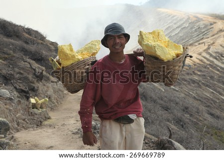 KAWAH IJEN, INDONESIA - AUGUST 10, 2011: Miner carries baskets with sulphur in fumes of toxic volcanic gas from sulphur mines in the crater of the active volcano of Kawah Ijen, East Java, Indonesia. - stock photo