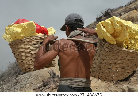KAWAH IJEN, INDONESIA - AUGUST 8, 2011: Miner carries baskets with sulphur in fumes of toxic volcanic gas from sulphur mines in the crater of the active volcano of Kawah Ijen, East Java, Indonesia. - stock photo