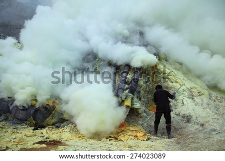 KAWAH IJEN, INDONESIA - AUGUST 9, 2011: Miner collects sulphur in the fumes of toxic volcanic gas at the sulphur mines in the crater of the active volcano of Kawah Ijen, East Java, Indonesia. - stock photo