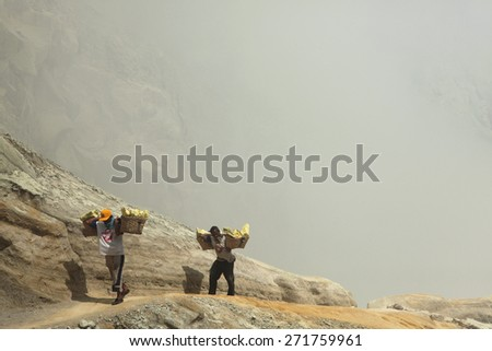 KAWAH IJEN, INDONESIA - AUGUST 8, 2011: Miners carry baskets with sulphur in fumes of toxic volcanic gas from the sulphur mines in the crater of the active volcano of Kawah Ijen, East Java, Indonesia. - stock photo