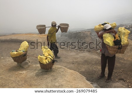 KAWAH IJEN, INDONESIA - AUGUST 8, 2011: Miners carry baskets with sulphur in toxic volcanic gas from the sulphur mines in the crater of the active volcano of Kawah Ijen, East Java, Indonesia. - stock photo