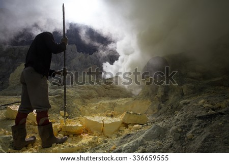 KAWAH IJEN, INDONESIA - OCT 12: Worker at sulfur mine inside Ijen crater on October 12, 2015. Miners are extracting gaseous sulfur going out in the mine of the crater