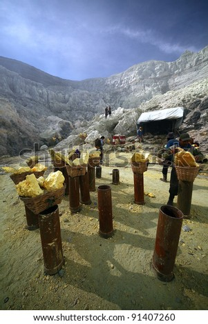 KAWAH IJEN, INDONESIA - SEPT 18 : Temporary raw sulfur station next to the hazardous mine in Kawah Ijen on 18 Sept 2010. Miner risk their life daily to carry these 80-100kg load to a nearby sugar factory - stock photo