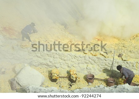 KAWAH IJEN, INDONESIA - SEPT 19 : Unidentified miners harvest raw sulphur from the crater of Kawah Ijen volcano in hazardous working environment with minimal protection on 19 Sept 2010 in Kawah Ijen. - stock photo