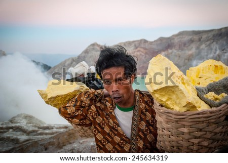 KAWAH IJEN, INDONESIA - SEPTEMBER 17: Miner carying baskets of around 60 kg of sulphur up from the Kawah Ijen volcanic crater in early morning. Taken Java, Indonesia on September 17, 2014. - stock photo