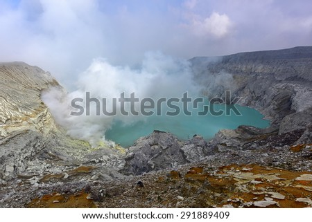 Kawah Ijen volcanic crater emitting sulphuric gas still used for sulphur mining in East Java, Indonesia - stock photo