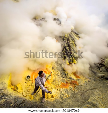 KAWAH IJEN VOLCANO, EAST JAVA, INDONESIA - MAY 25, 2013: Sulfur miner collecting hunks of solid sulfur inside the crater of Kawah Ijen volcano in East Java, Indonesia. - stock photo