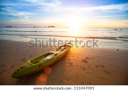 Kayak at the tropical beach at beautiful sunset. - stock photo
