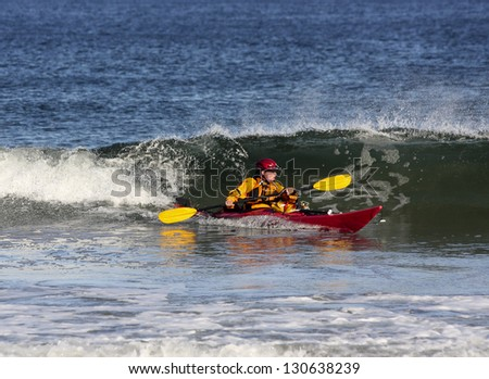 Kayak coming out from  the crest of a wave in rough sea of Nova Scotia coast, Canada - stock photo