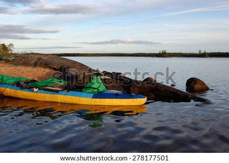 Kayak is moored on the bank of the lake against big stones. Karelia, Russia. - stock photo
