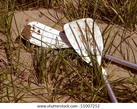 Kayak Oars Sitting In Sand and Grass - stock photo