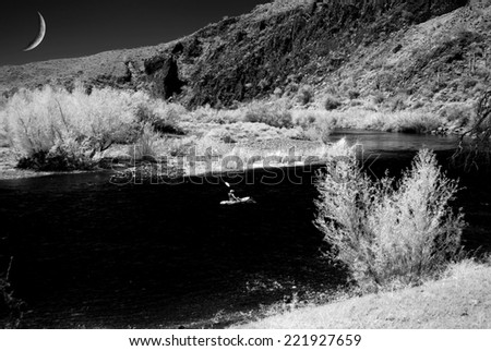 Kayak on desert river with crescent moon - stock photo