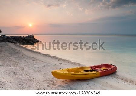 Kayak on the tropical beach at sunset - stock photo