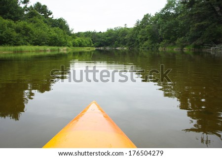Kayak paddling on river through woods.